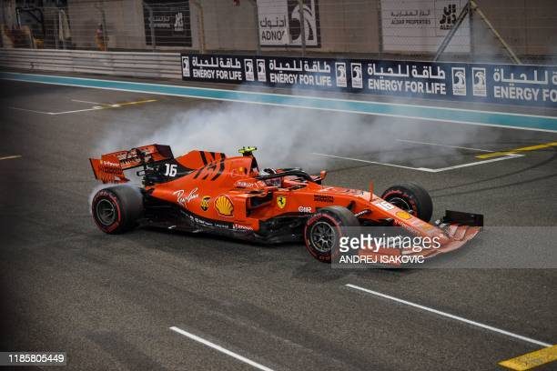 Ferrari's Monegasque driver Charles Leclerc performs doughnuts as he celebrates his third place finish at the Yas Marina Circuit in Abu Dhabi after...