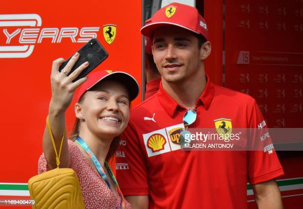 Ferrari's Monegasque driver Charles Leclerc poses for a photo with a fan at the paddock of the Formula One Singapore Grand Prix at the Marina Bay...
