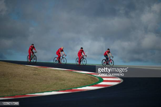 Ferrari's Monegasque driver Charles Leclerc rides a bicycle with members of his team at the Algarve International Circuit in Portimao on October 22,...
