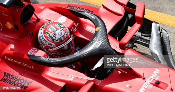 Ferrari's Monegasque driver Charles Leclerc sits in his car as Ferrari mechanics work on it in the pit lane during a practice session at the...