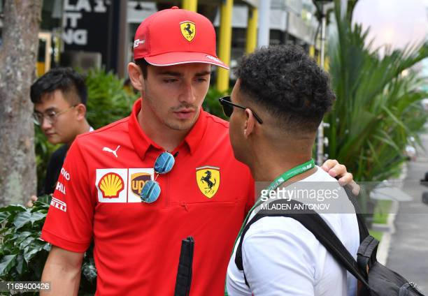 Ferrari's Monegasque driver Charles Leclerc talks to a fan at the paddock of the Formula One Singapore Grand Prix at the Marina Bay Street Circuit in...