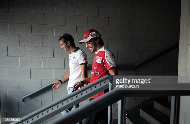 Ferrari's Spanish driver Fernando Alonso and Lotus racing's Italian driver Jarno Trulli leave after a press conference at the Monza Autodrome circuit...