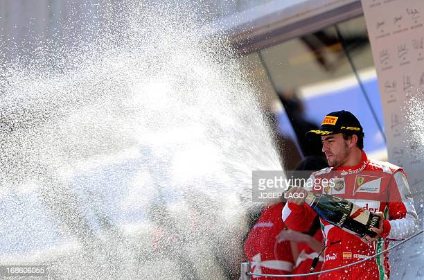 Ferrari's Spanish driver Fernando Alonso celebrates on the podium at the Circuit de Catalunya in Montmelo near Barcelona on May 12, 2013 after the...