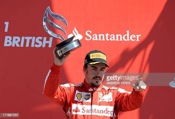 Ferrari's Spanish driver Fernando Alonso celebrates on the podium at the Silverstone circuit in Silverstone on June 30, 2013 after the British...