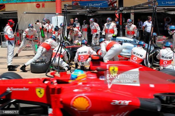 Ferrari's Spanish driver Fernando Alonso leaves the pits passing McLaren Mercedes' British driver Lewis Hamilton at the Valencia Street Circuit on...