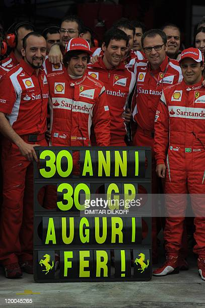 Ferrari's Spanish driver Fernando Alonso poses with team members to celebrate his 30th birthday in the pits at the Hungaroring circuit on July 29...