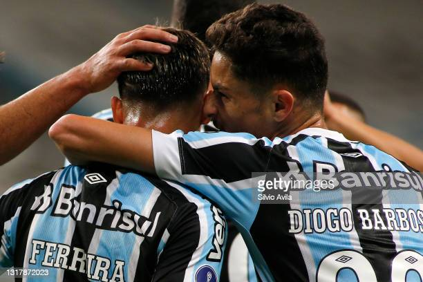 Ferreira of Gremio celebrates with teammate Diogo Barbosa after scoring the third goal of his team during a match between Gremio and Lanus as part of...