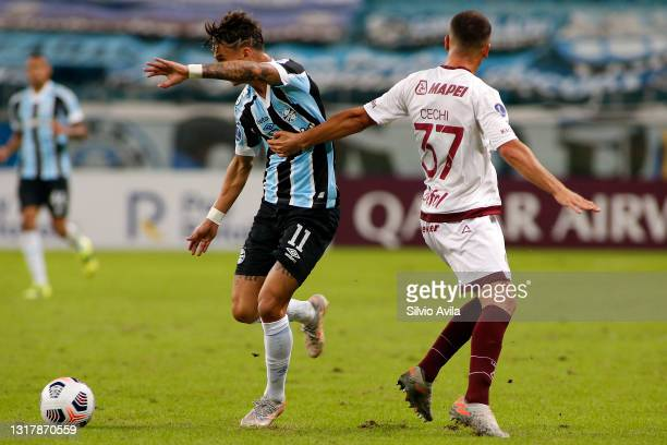 Ferreira of Gremio competes for the ball with Ignacio Cechi of Lanus during a match between Gremio and Lanus as part of group H of Copa CONMEBOL...