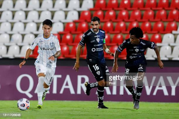 Ferreira of Gremio drives the ball while followed by Cristian Pellerano and José Hurtado Cheme of Independiente del Valle during a third round first...