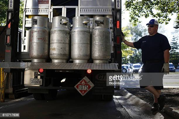 A Ferrellgas Partners LP employee waits as propane tanks are loaded onto a delivery truck outside a business in Louisville Kentucky US on Tuesday...