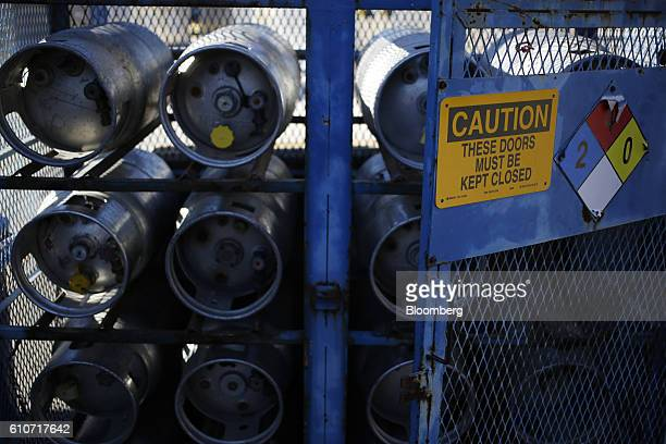 Ferrellgas Partners LP propane tanks sit inside a safety unit outside a business in Louisville Kentucky US on Tuesday Sept 27 2016 Ferrellgas is...