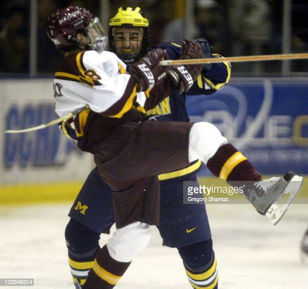 Ferris State forward Mark Bomersback gets hit by a Michigan player during third period action at Yost Ice Arena in Ann Arbor Michigan on November 8...