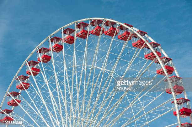 ferris wheel against blue sky with white clouds - 観覧車 ストックフォトと画像
