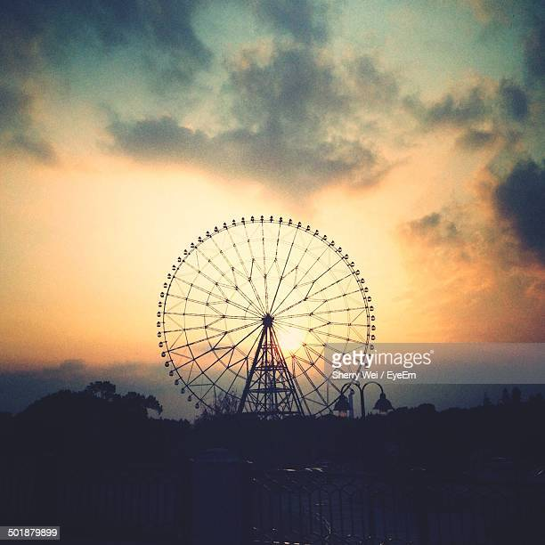 Ferris wheel against cloudy sky during sunset