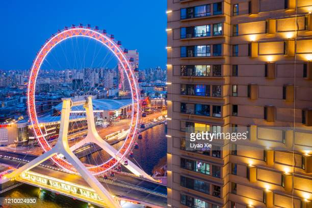 ferris wheel along the residential building - liyao xie stock pictures, royalty-free photos & images