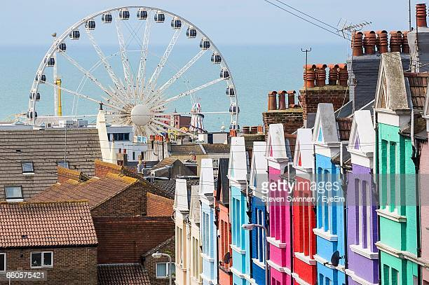 ferris wheel and colorful buildings against sea - brighton england stock pictures, royalty-free photos & images