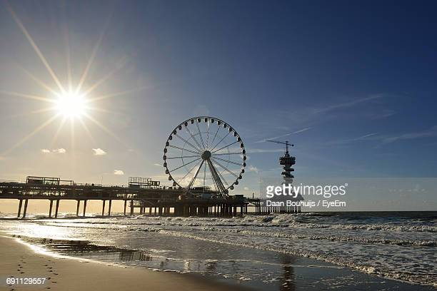 ferris wheel and pier by sea against sky - hague stock photos and pictures