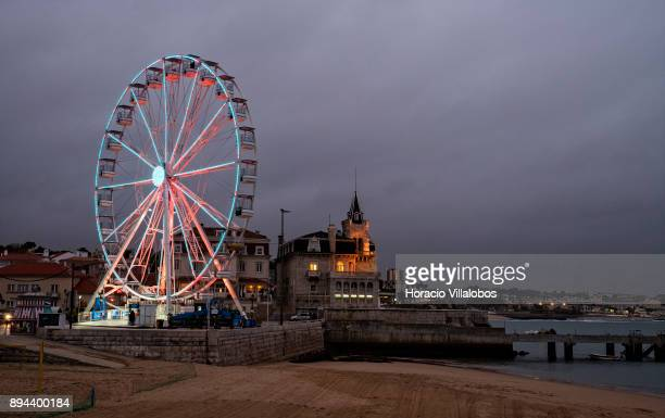 Ferris wheel and Seixas Palace are seen facing Praia da Baia at dusk on December 14 2017 in Cascais Portugal The ferris wheel has been set up as part...