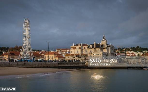 Ferris wheel and Seixas Palace are seen facing Praia da Baia at the end of afternoon on December 14 2017 in Cascais Portugal The ferris wheel has...