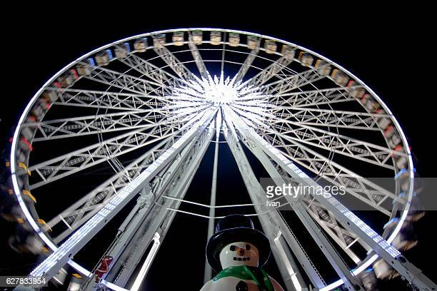 Ferris Wheel and Snowman in Amusement Park at Night