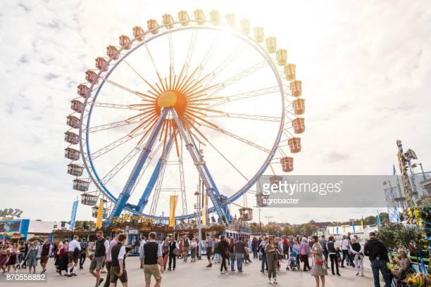 Riesenrad und Besucher zu Fuß durch Oktoberfest Messegelände, München, Deutschland