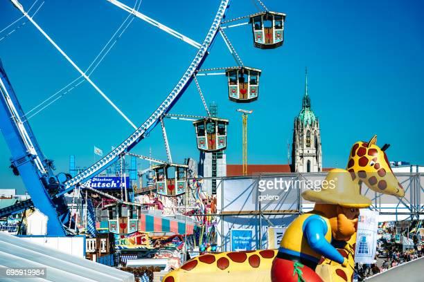 Riesenrad auf dem Oktoberfest in München mit Skyline im Hintergrund