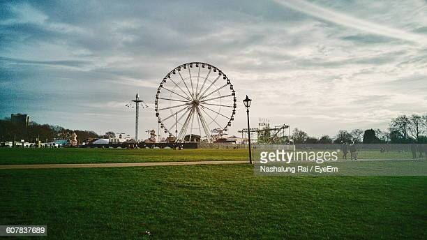 Ferris Wheel At Park Against Cloudy Sky
