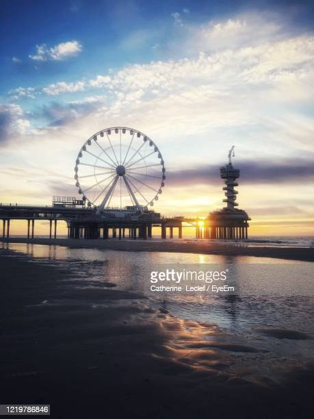 ferris wheel at sea against cloudy sky - the hague stock pictures, royalty-free photos & images