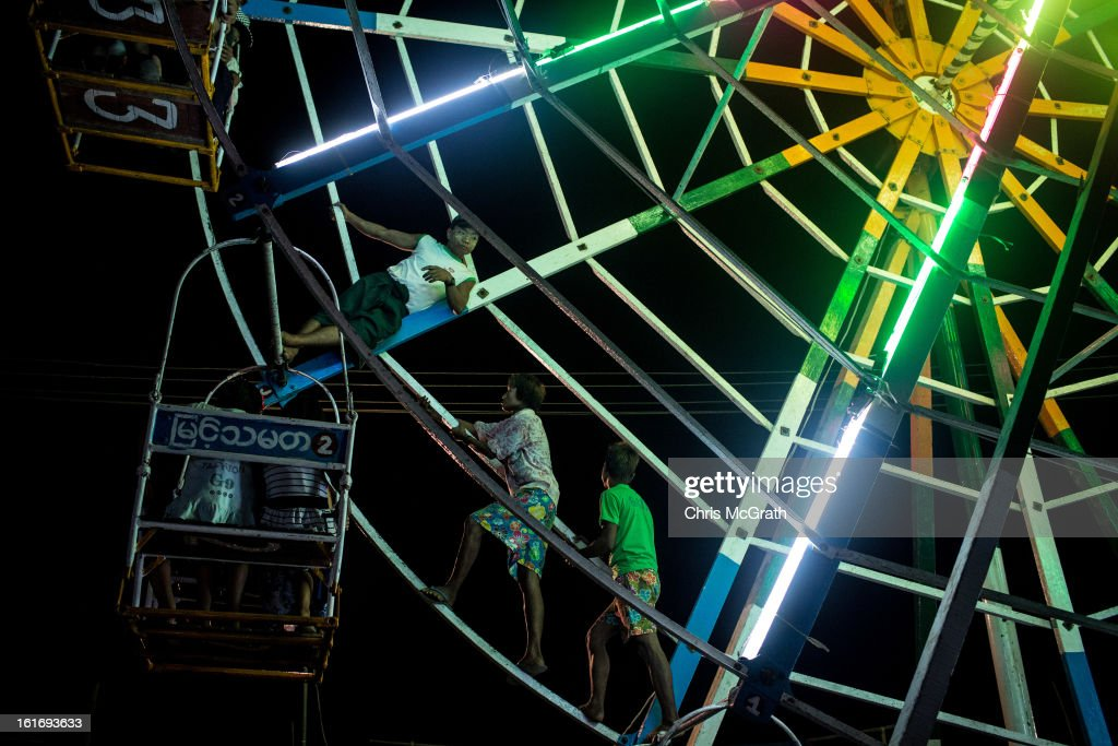 Ferris wheel attendants walk up the inside of the wheel to make it spin at a rural carnival in South Dagon Township on February 14, 2013 in Yangon, Burma. The ferris wheel is man powered and takes seven men to spin it for their customers. Myanmar is going through rapid political and economic reforms initiated by the countries first civilian president Thein Sein after years of military junta rule.