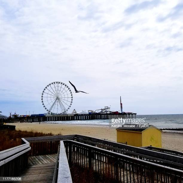 ferris wheel by pier at sea against cloudy sky - atlantic city stock pictures, royalty-free photos & images