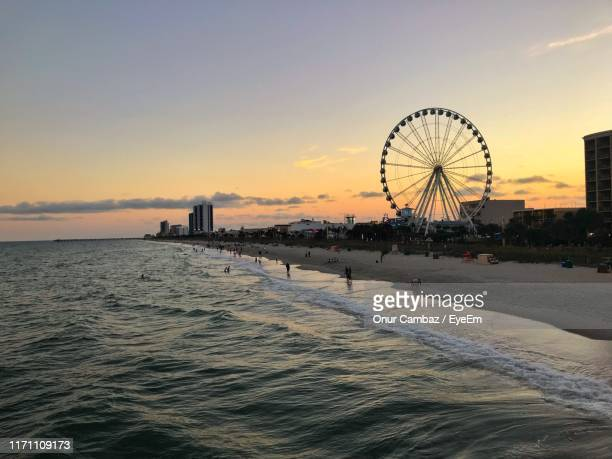 ferris wheel by sea against sky during sunset - file:myrtle_beach,_south_carolina.jpg stock pictures, royalty-free photos & images