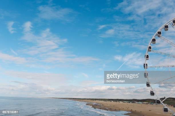 ferris wheel by sea against sky - bortes cristian stock-fotos und bilder