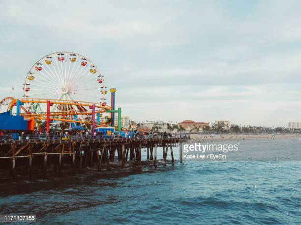 ferris wheel in city by sea against sky - la waterfront stock pictures, royalty-free photos & images