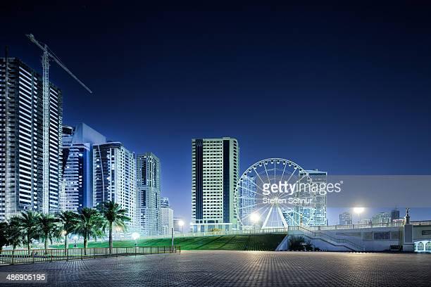 Ferris wheel in front of skyscrapers