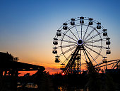 Ferris wheel in sunset.  Big wheel with cabins