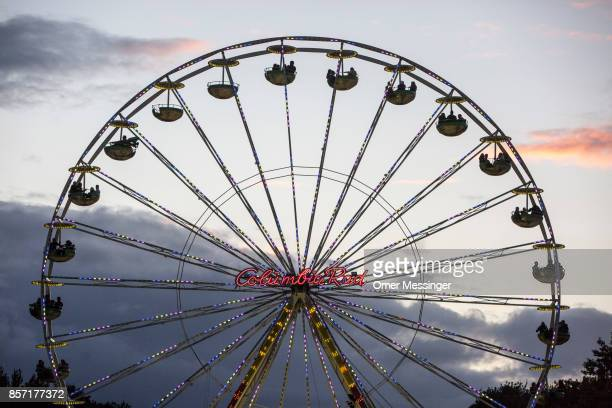 A ferris wheel is seen at dusk at an amusement area set up along 17th of June Street in Tiergraten Park near the Brandenburg Gate on German Unity Day...