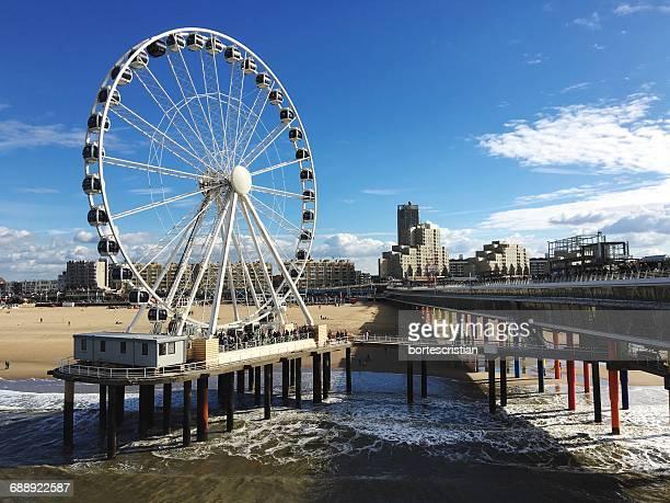 Ferris Wheel On Pier At Beach Against Blue Sky
