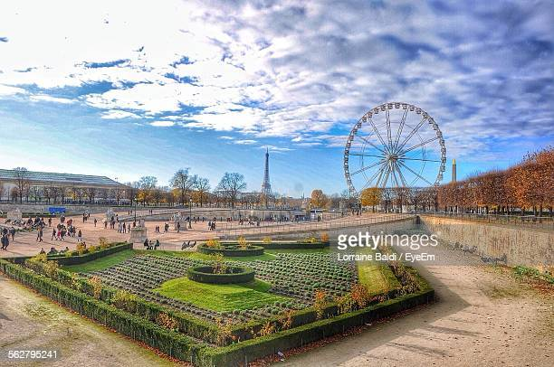 Ferris Wheel With Eiffel Tower In Background Against Cloudy Sky