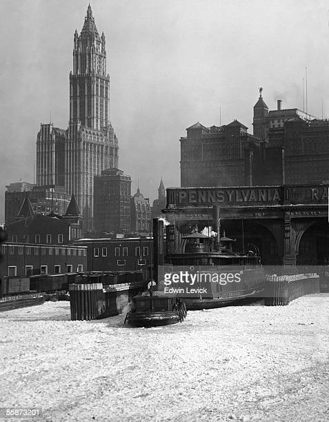 A ferry boat floats on the icy water of the Hudson River at a terminal in southern Manhattan New York New York circa 1915 The Woolworth Building is...