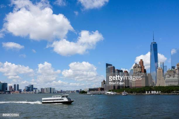 a ferry boat in front of the new york skyline - schiffstaxi stock-fotos und bilder