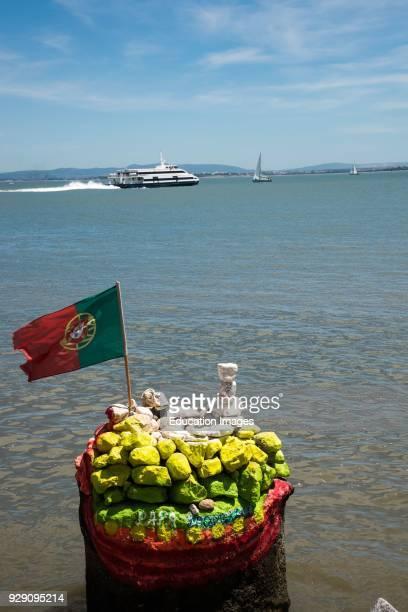 Ferry boat passes colorful rock pile Tagus River Lisbon Portugal