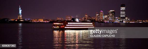 a ferry boat passes in front of statue of liberty with manhattan on the background - claudio capucho stock pictures, royalty-free photos & images