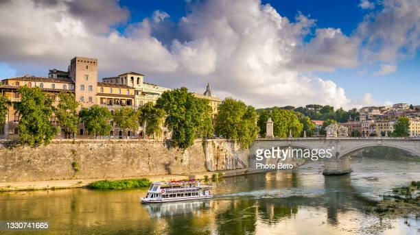 a ferry boat sails along the tiber river in the light of the sunset in the heart of rome - international match stock pictures, royalty-free photos & images