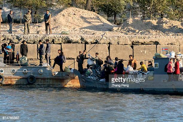 Ferry boat transporting people and living goods arrives at a dock beside Yalu river at North Korea side of border. Sinuiju, facing Chinese Dandong...