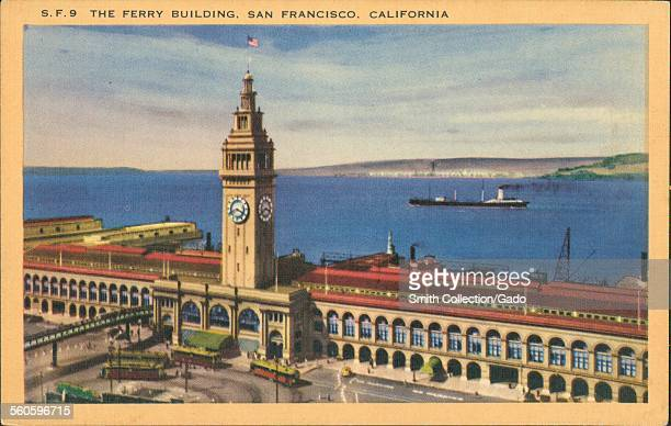 Ferry building with clock tower and view of San Francisco bay and harbor Angel Island visible in the distance with street cars in the foreground San...