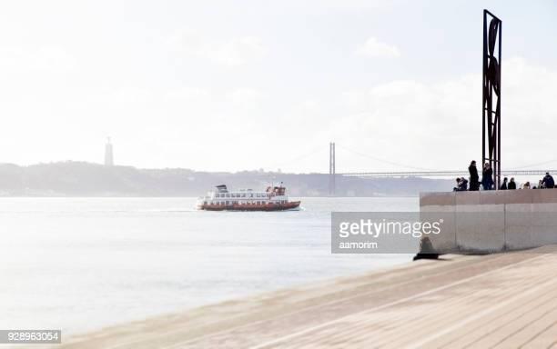 ferry crossing tagus river in lisbon - statua di cristo re foto e immagini stock