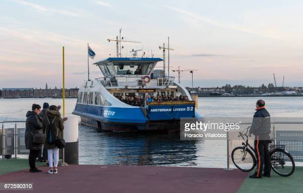 A ferry from Central Station arrives in NDSM at dusk on April 19 2017 in Amsterdam Netherlands GVB ferries crisscross the city's waterfront carrying...