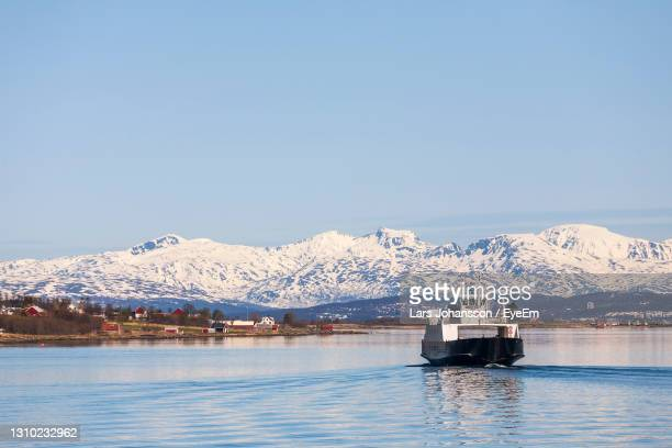 ferry in a norwegian fjord with snow capped mountains in the spring - ferry stock pictures, royalty-free photos & images