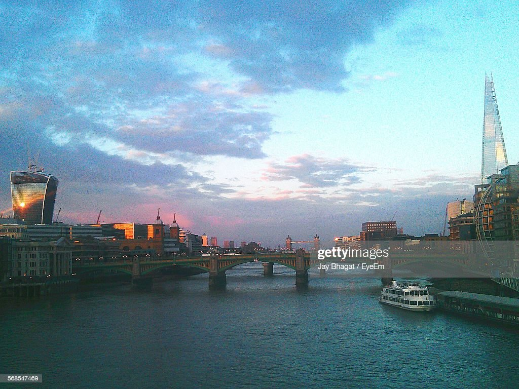Ferry Moving On River By Bridge Amidst Buildings Against Cloudy Sky : Stock Photo