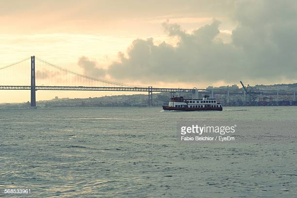 Ferry Moving On Tagus River By April 25Th Bridge Against Cloudy Sky